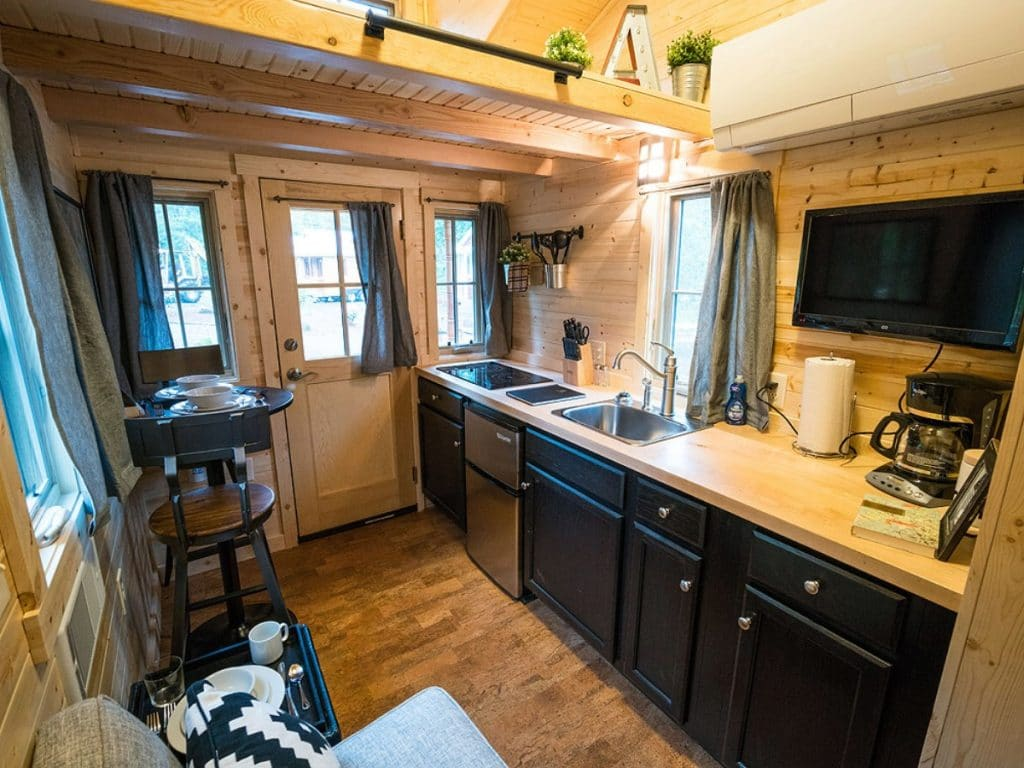 Tiny home kitchenette with dark blue cabinets and dorm refrigerator