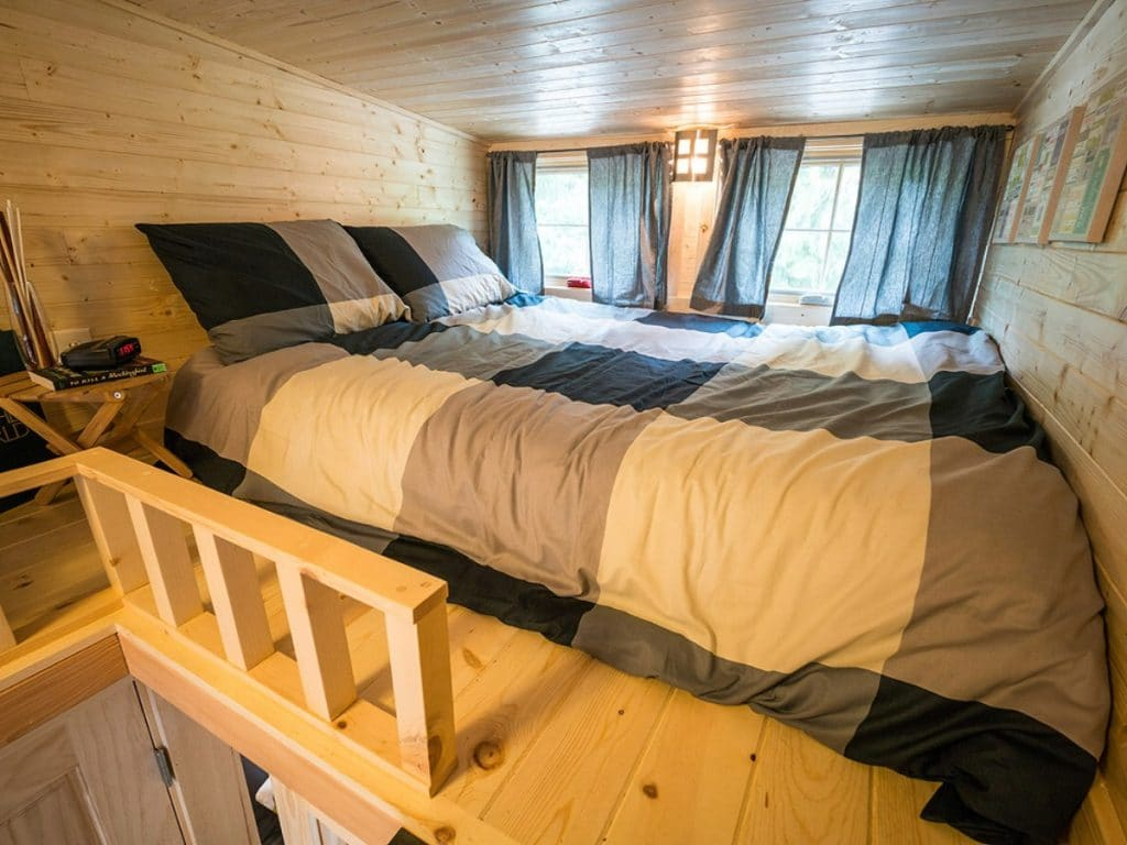 Loft with two windows and bed with wood rail