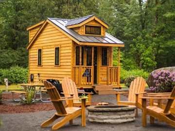 Tiny cabin with loft window and adirondack chair by fire pit