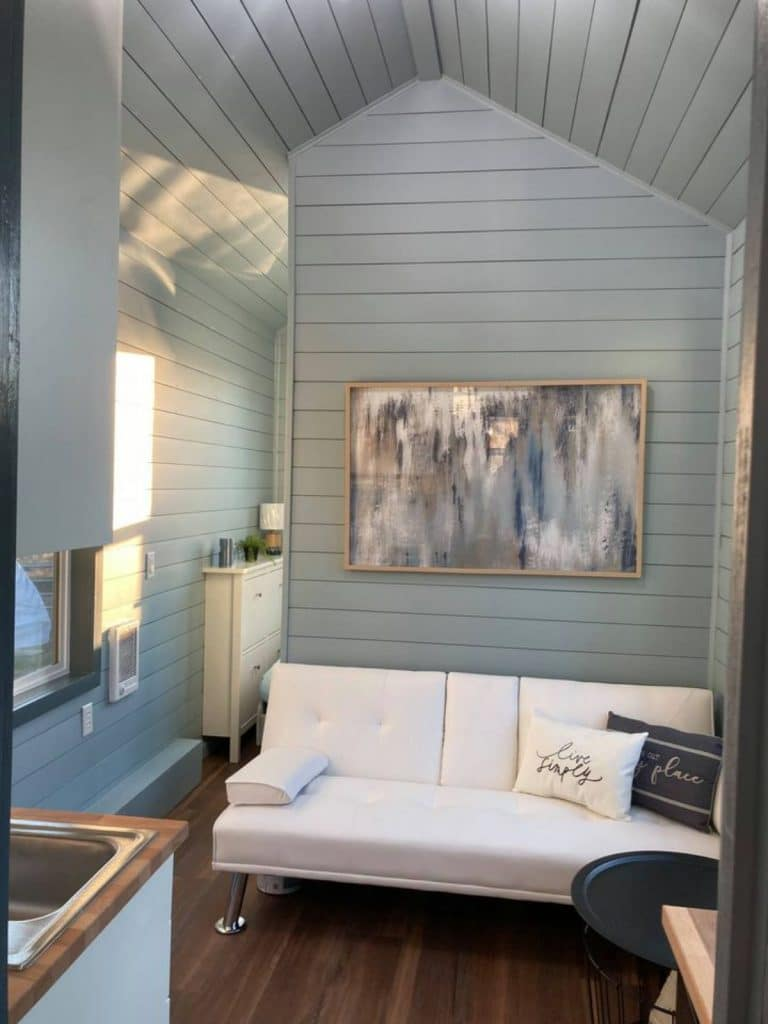 Tiny house living room with opening to tiny bedroom