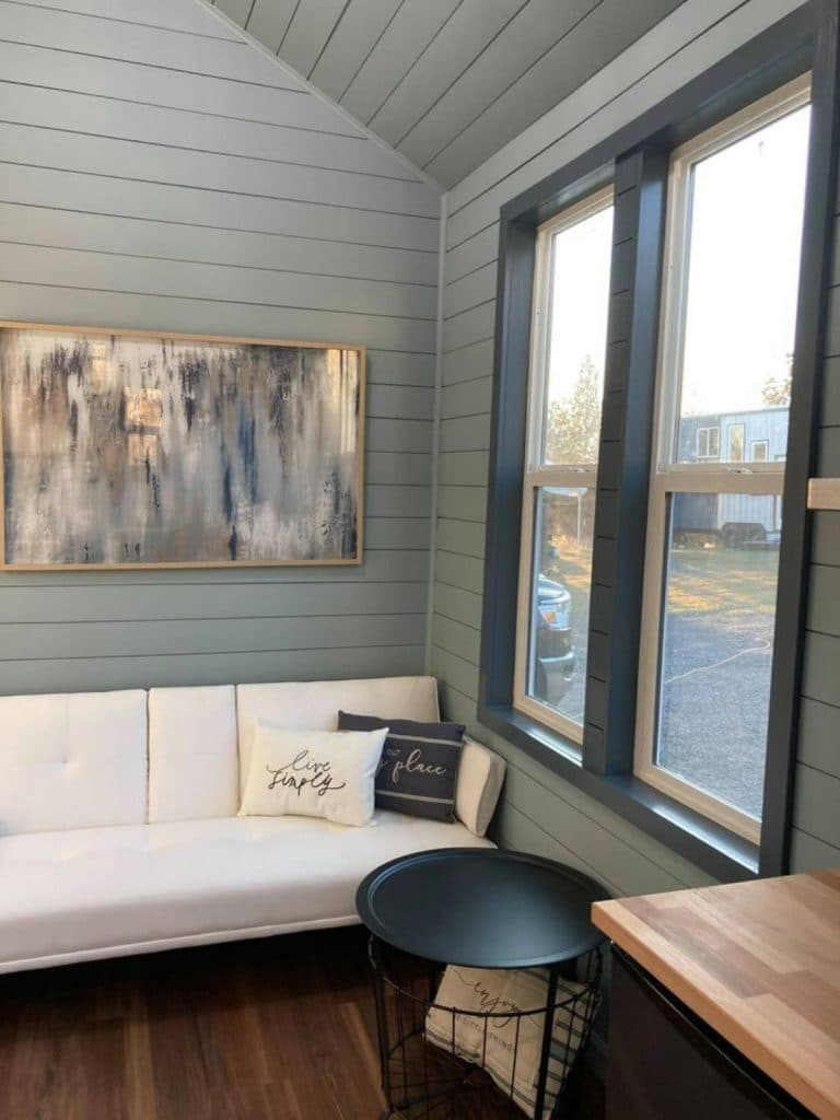 White sofa with picture above next to windows