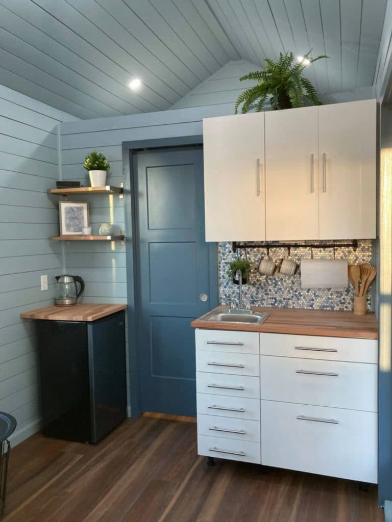 Blue walls with white cabinets and a small dark wood cabinet with coffee pot