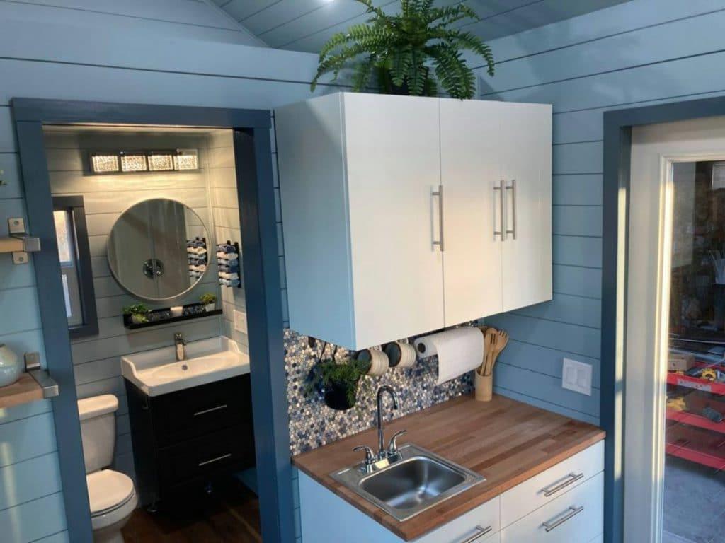 Bathroom door open next to white cabinets