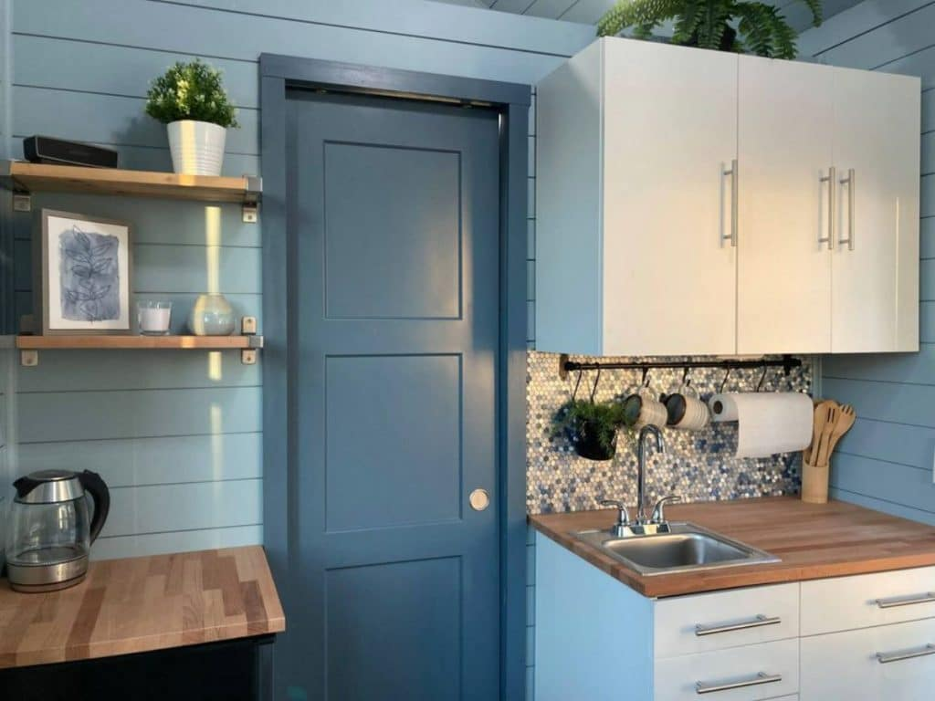 Blue door between white cabinets and floating shelves