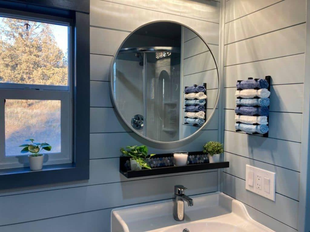 Round mirror above white deep sink