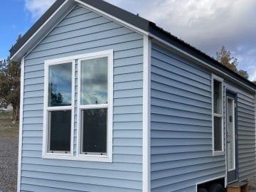 Blue tiny home with white trim around windows