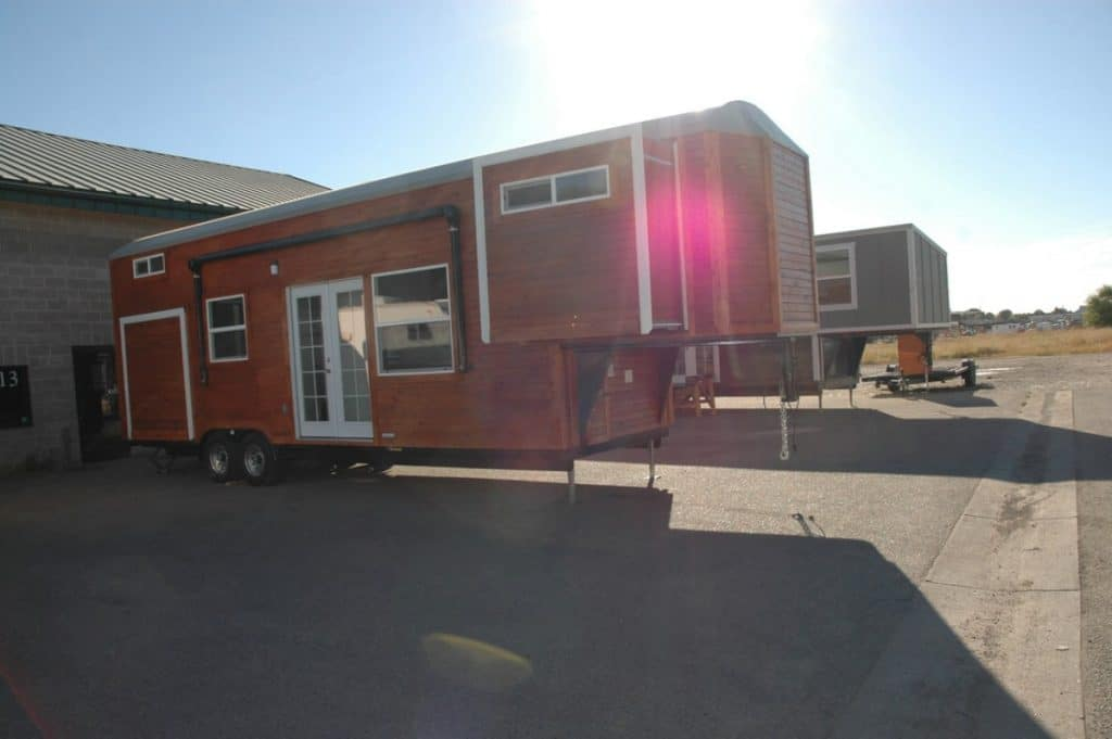 Front of tiny home with white trim and brown siding