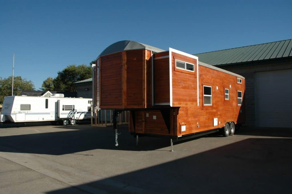 Back side of brown tiny home with slide out