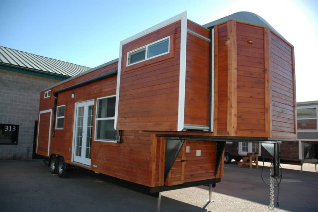 Carpathian tiny home with brown siding and white trim