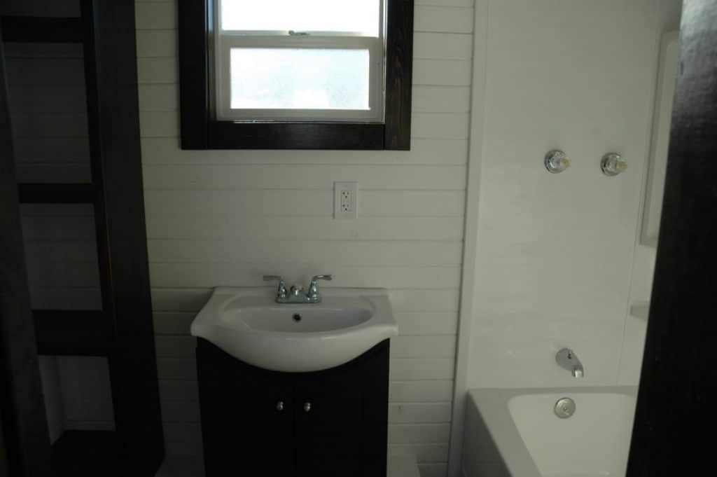 Bathroom vanity with dark wood trim and partial view of white shower
