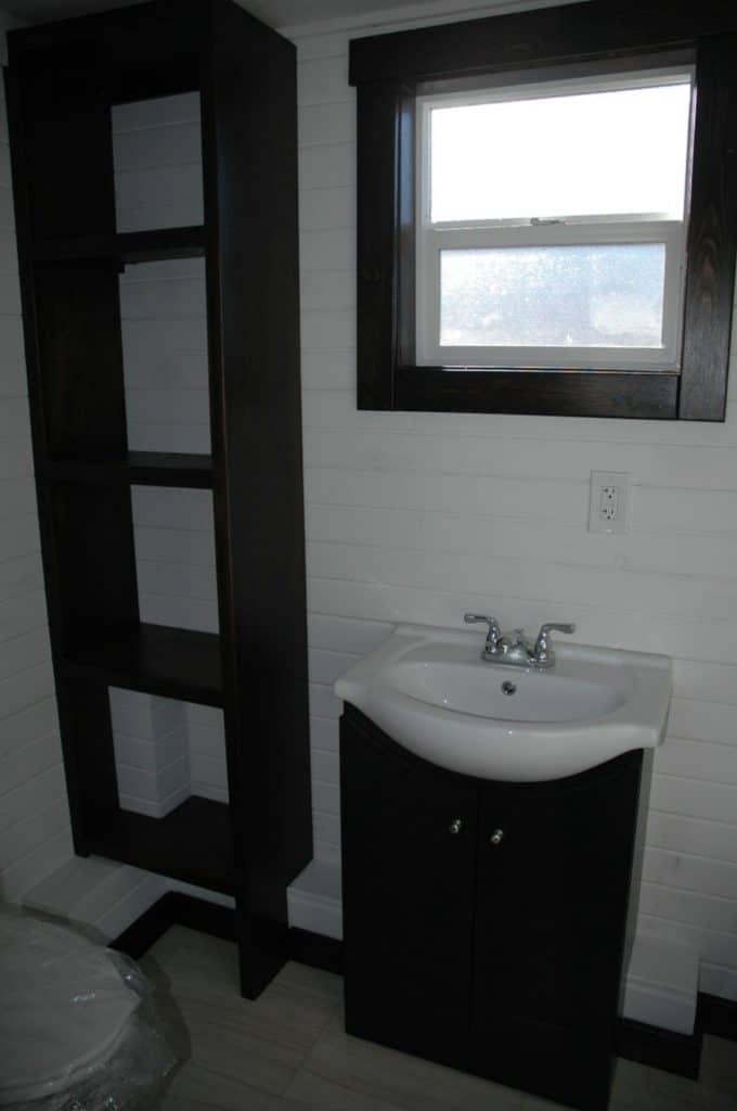 Bathroom vanity with dark wood shelf next to it