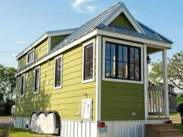 Green tiny house with white trim and small porch