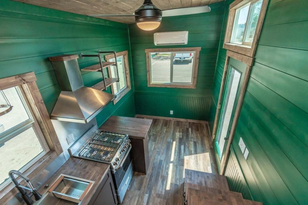 View into kitchen from tiny home loft with green walls