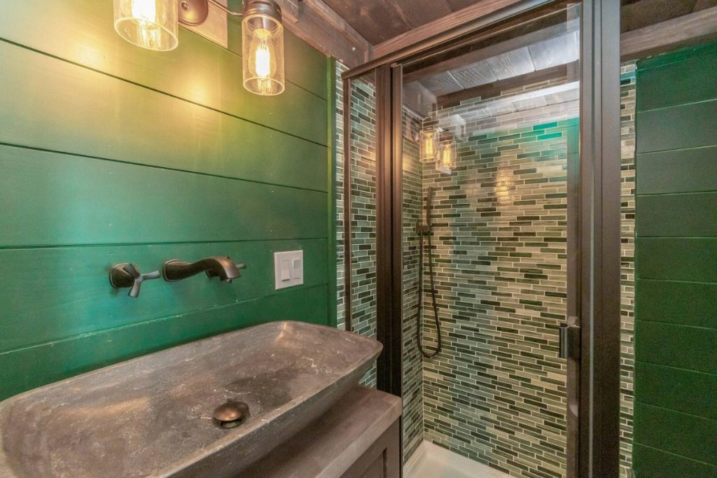 Stone sink by shower with white and green tile wall