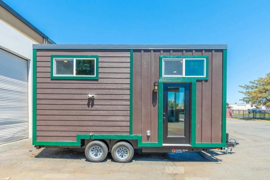 Brown and green tiny house on wheels in parking lot