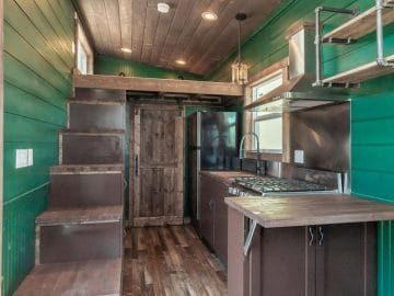 Kitchen in tiny house with green walls and dark wood stain floors