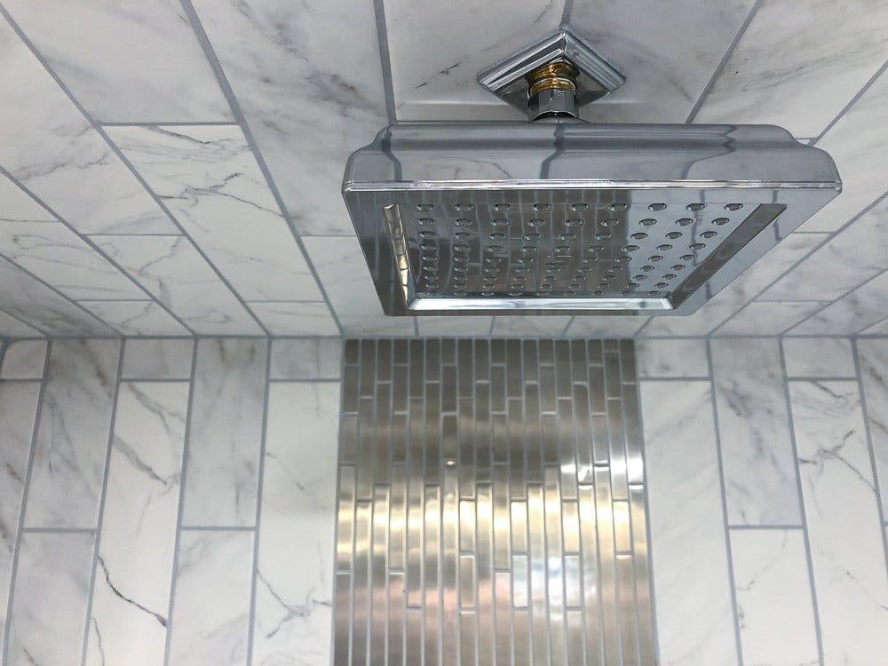 Large delta brand showerhead in marble tiled shower