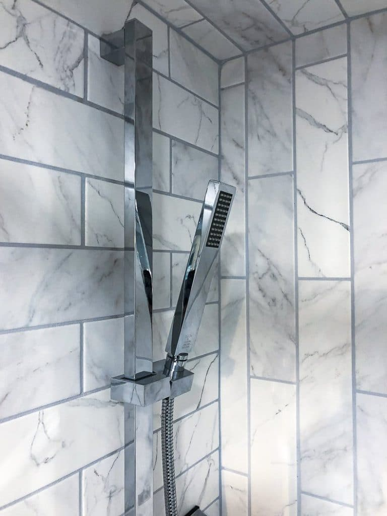 Delta shower head with detachable handle in marble tiled shower