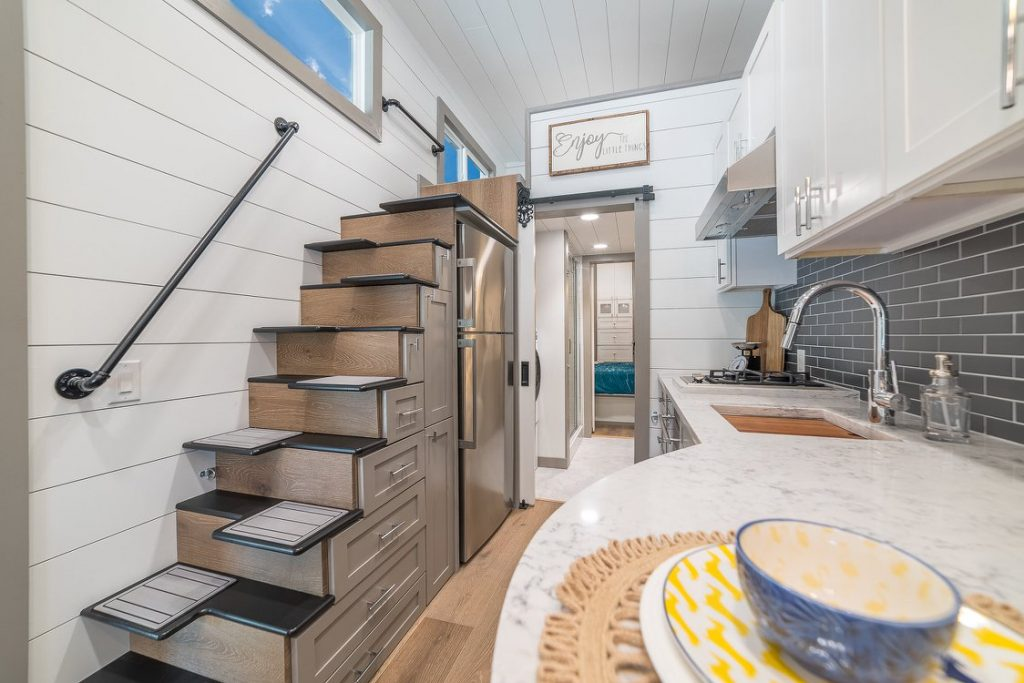 Living space in tiny home with wooden stairs