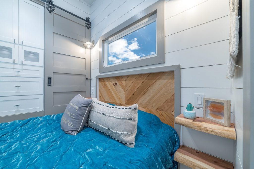 Bed with raw wood headboard and grey barnhouse door in background