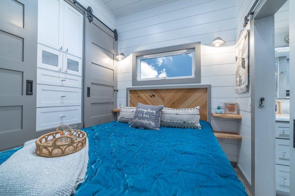 Teal blanket on queen bed in tiny bedroom
