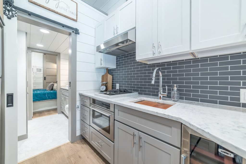 Farmhouse kitchen sink in grey cabinets with tile backsplash