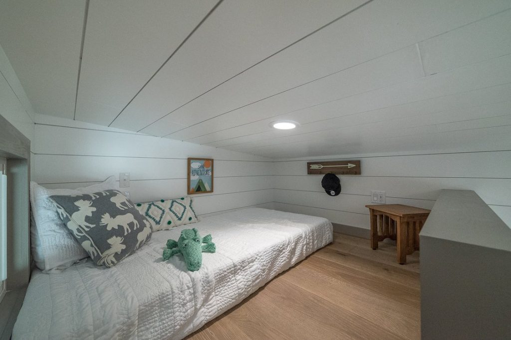 Bed in loft bedroom with white ceiling