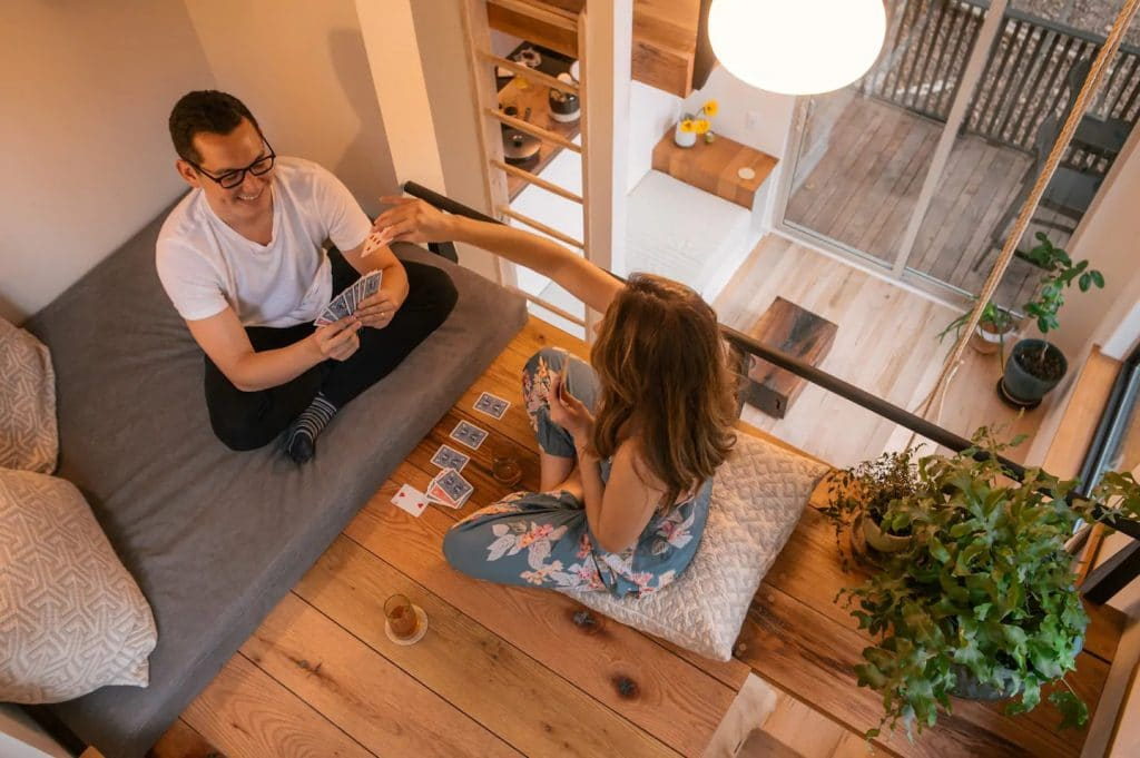 Couple sitting on cushions in loft playing cards