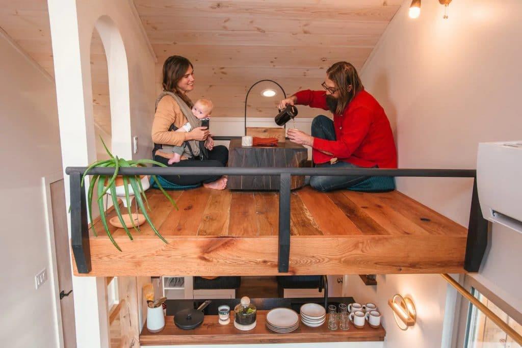 Couple and baby in loft having tea