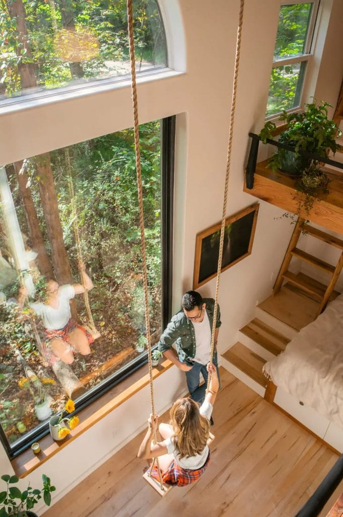 Indoor rope swing in front of large picture window
