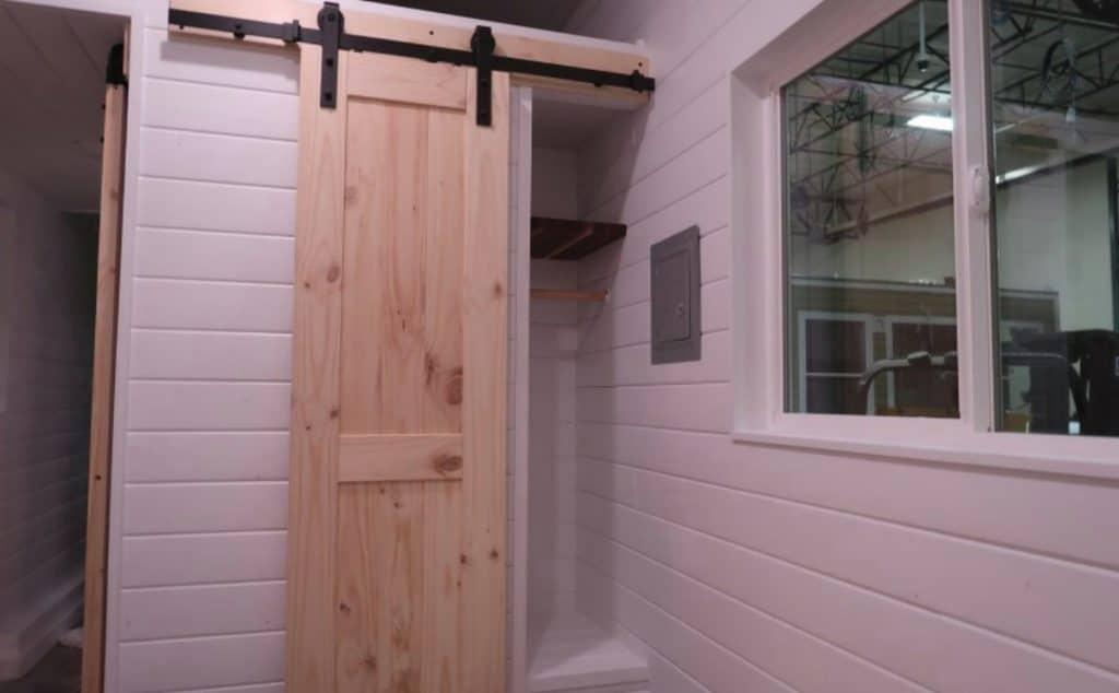 Wooden barn door in tiny home bedroom
