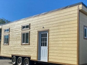 Tan tiny house on wheels with white door