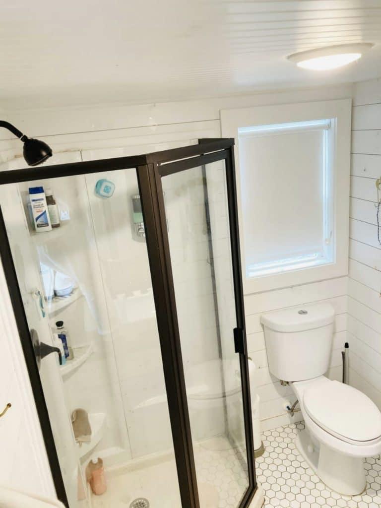 Corner shower with white shiplap wall surround