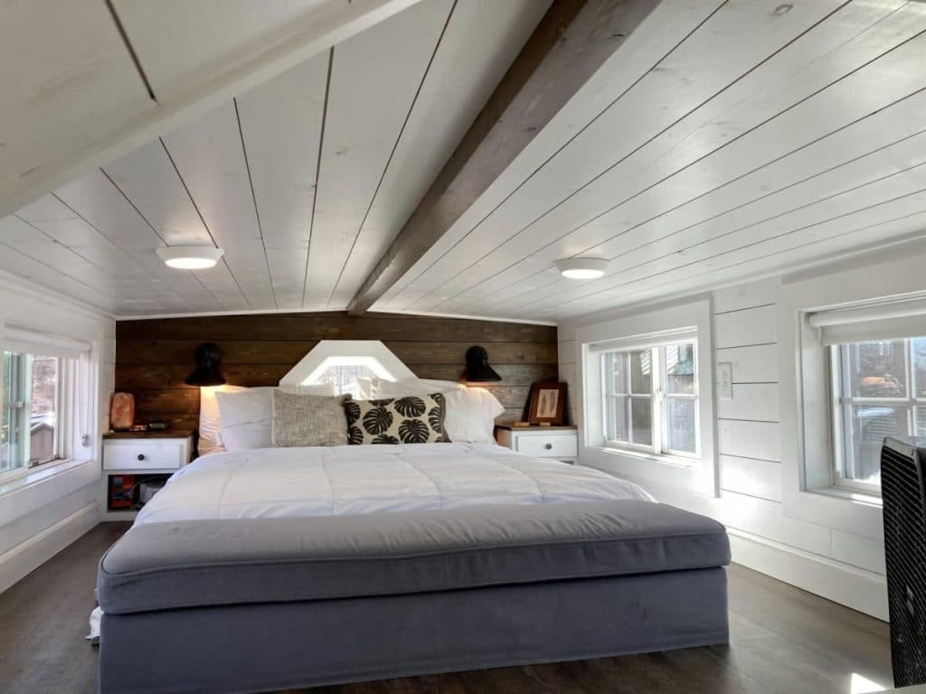 Bed against wood back wall in loft