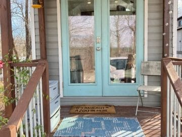 Tiny house front porch with light teal doors