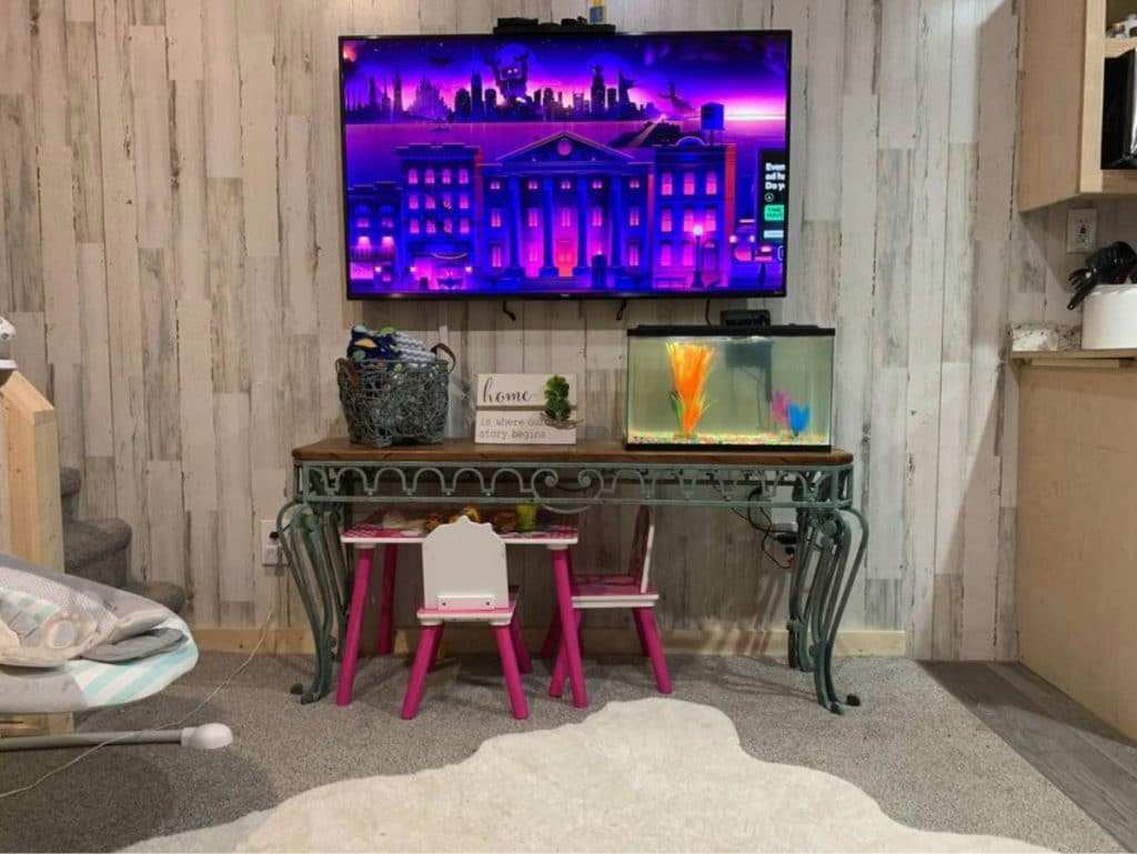 Television mounted on wood wall with dark wood table and fish tank below
