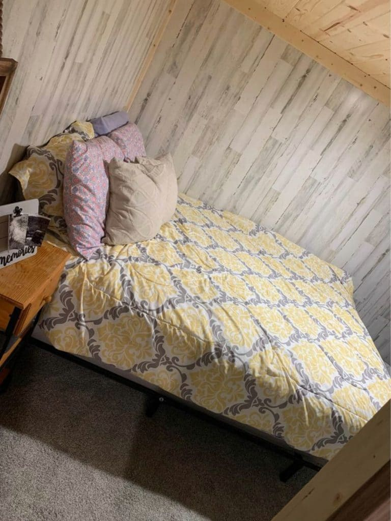 Yellow and blue bedding on bed in tiny house bedroom