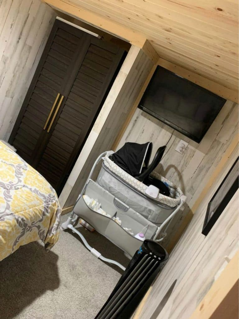 Tiny house closet with dark wood doors and corner with bassinet
