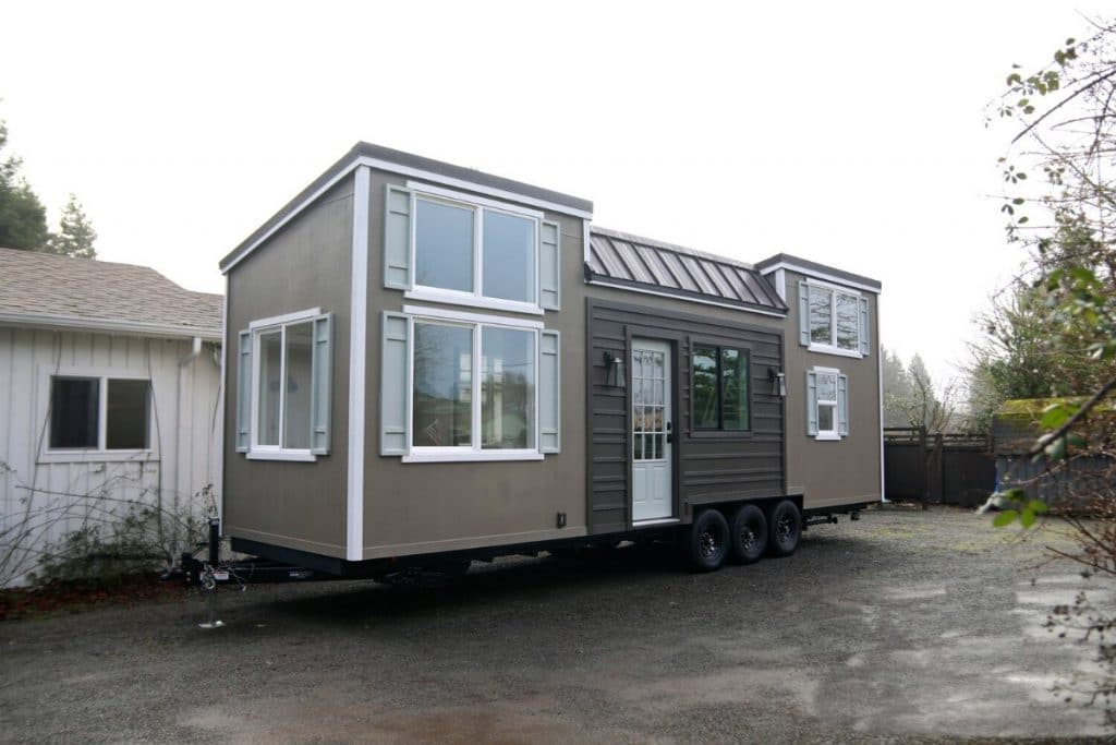 Brown tiny house on lot with white trim