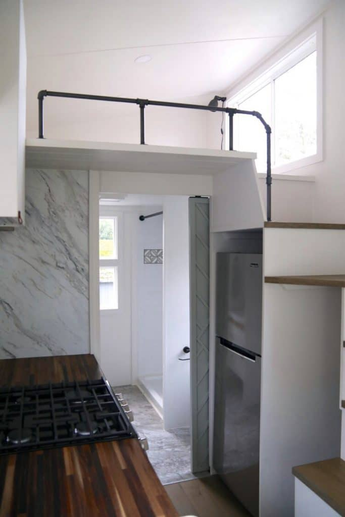 View of stainless steel refrigerator under stairs