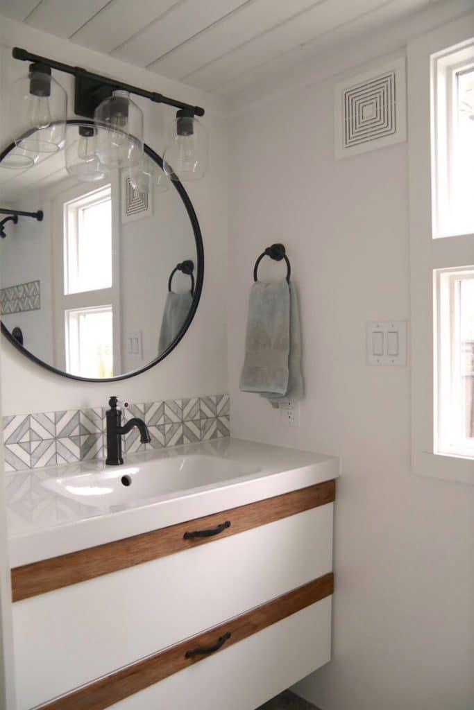 White vanity below round mirror with black trim