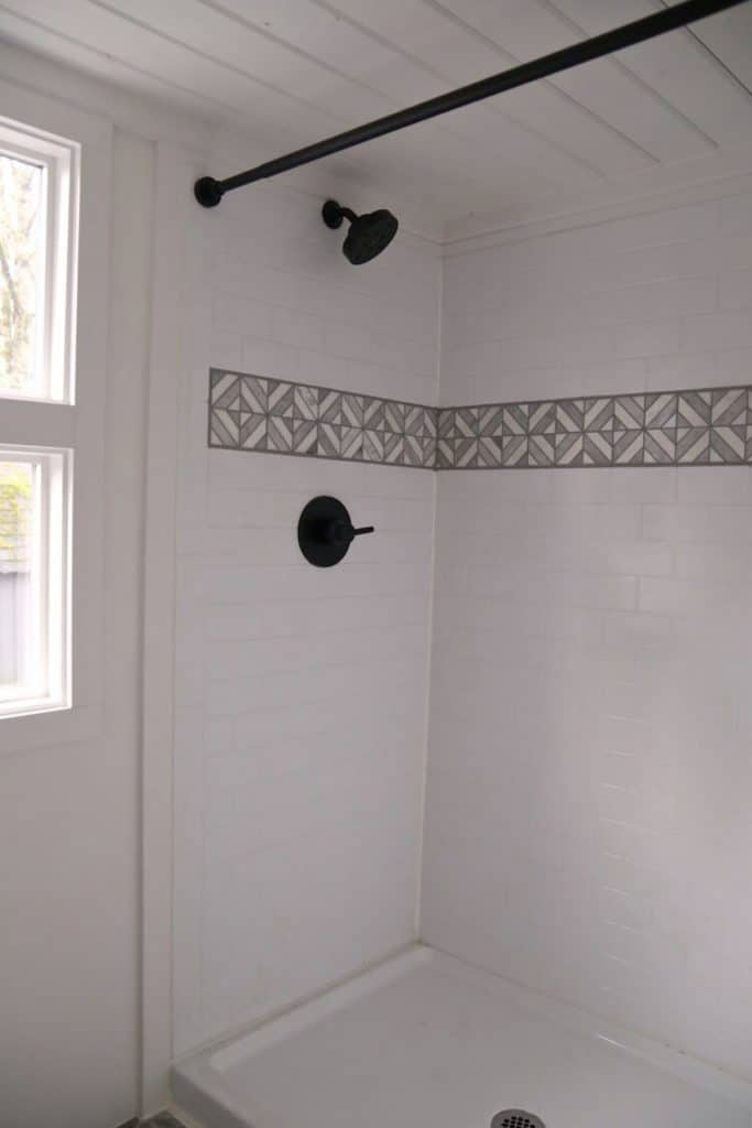 White tile shower with gray tile around the upper middle section