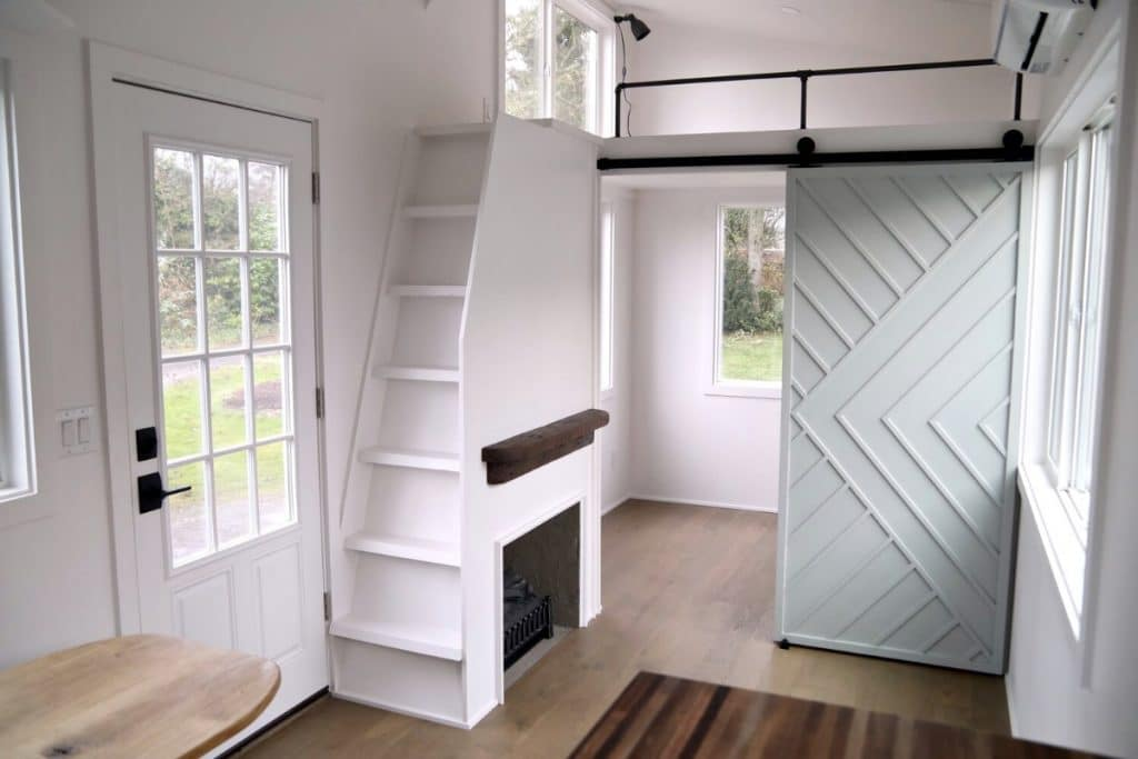 White stair case with fireplace below next to front door
