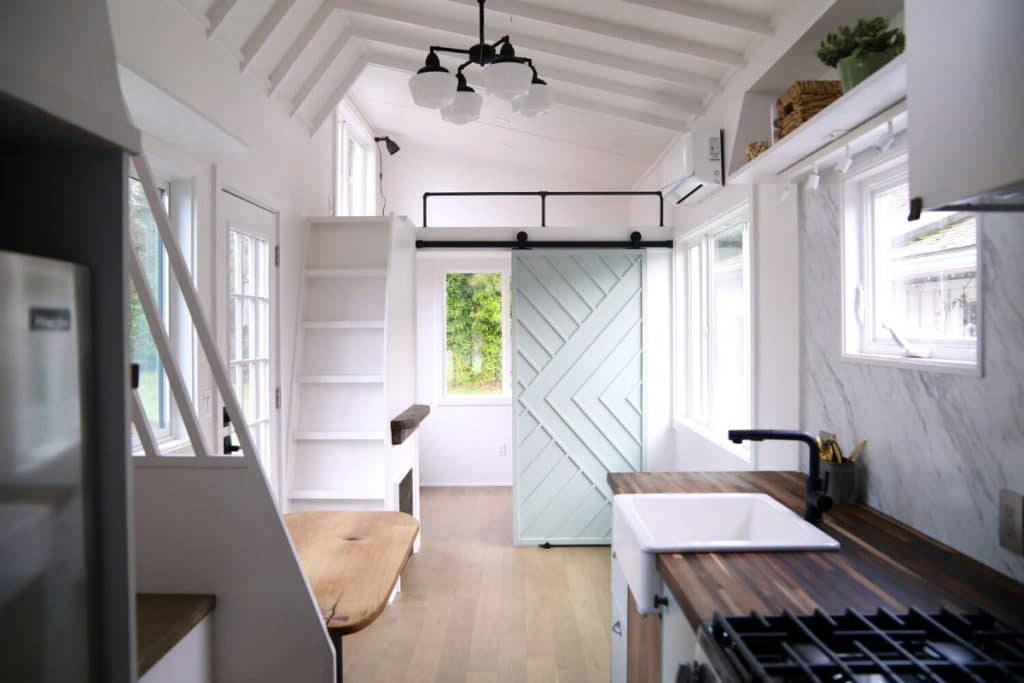 View toward bathroom of tiny house with light gray chevron door
