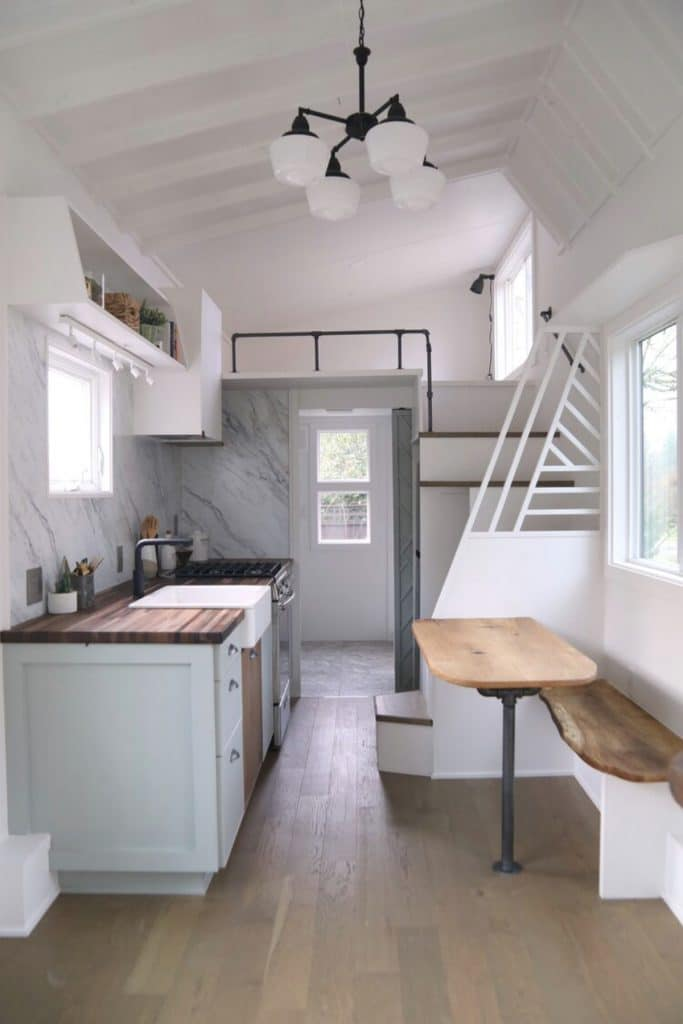 View into tiny house kitchen with sink on one side and table on opposite side