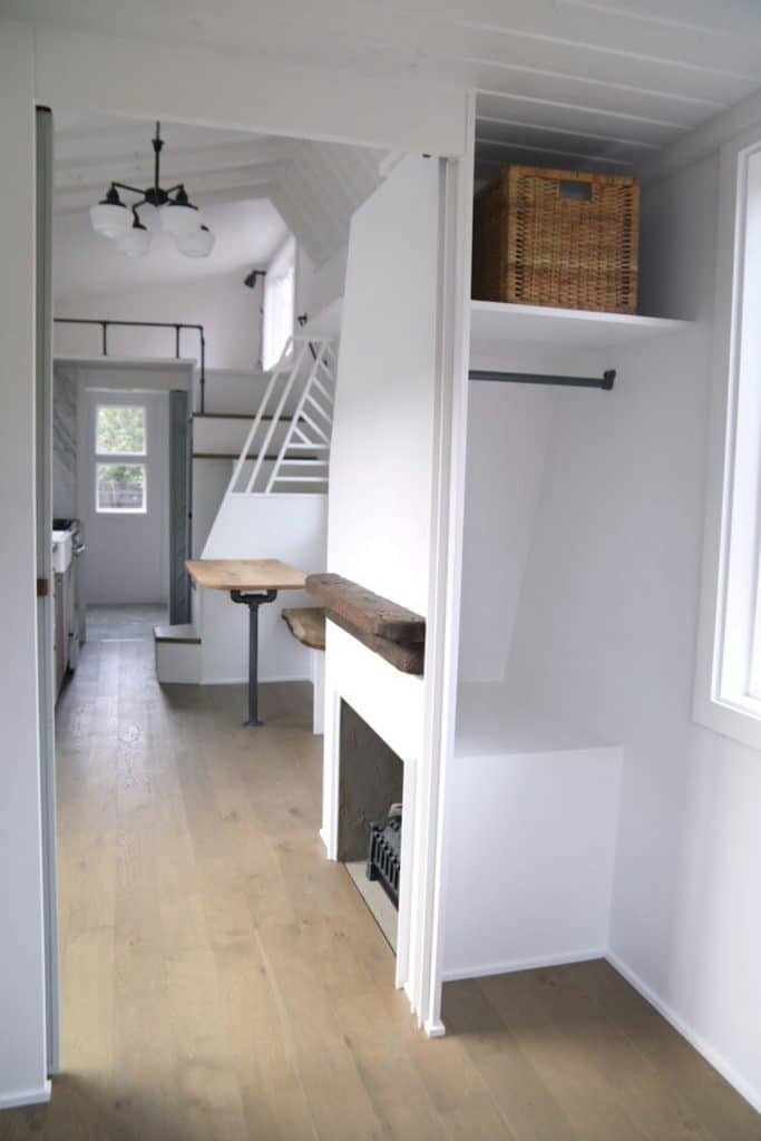 Closet behind fireplace and stairs with rod below shelf