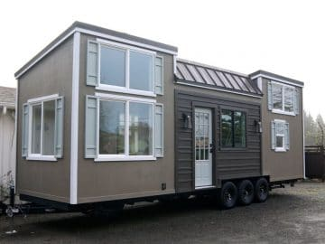Brown tiny house with two lofts and white trim