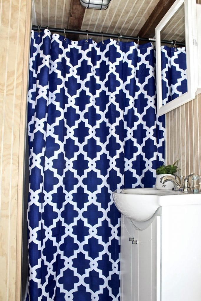 Tiny bathroom with blue and white shower curtain
