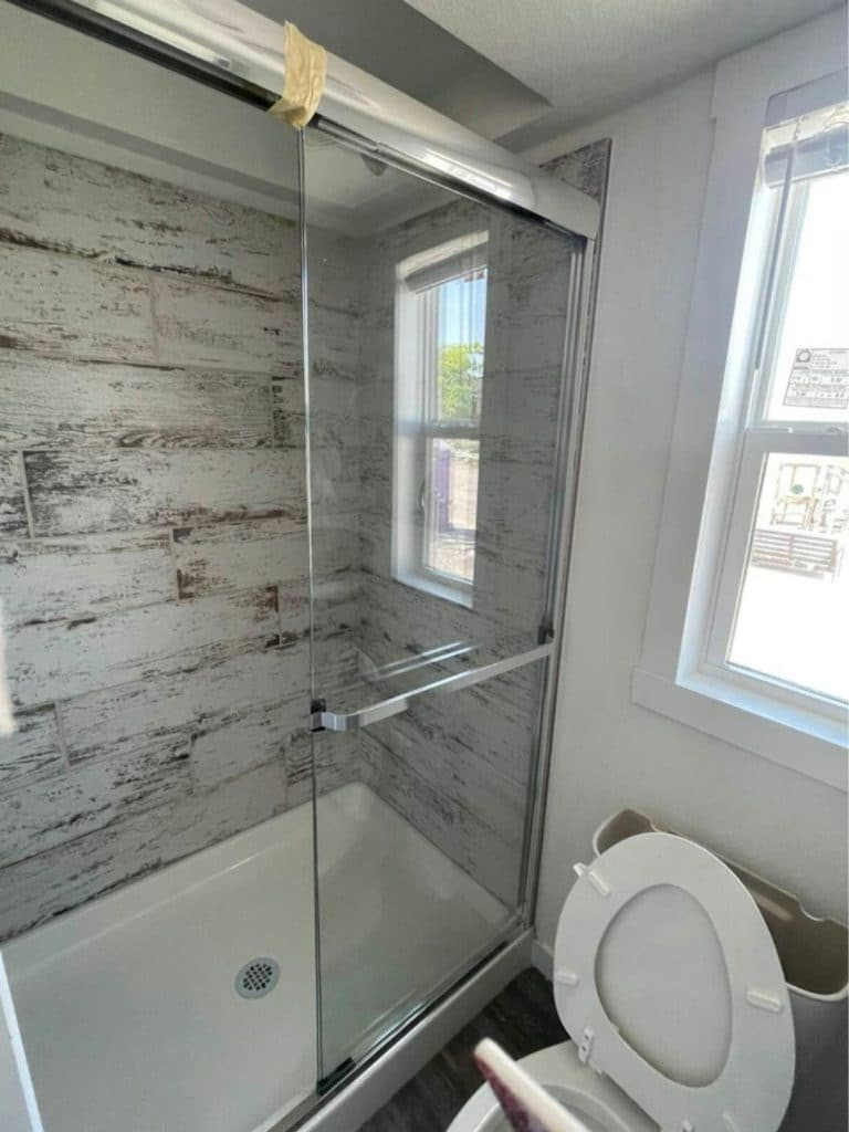 Gray tile lined shower with glass door and white bottom