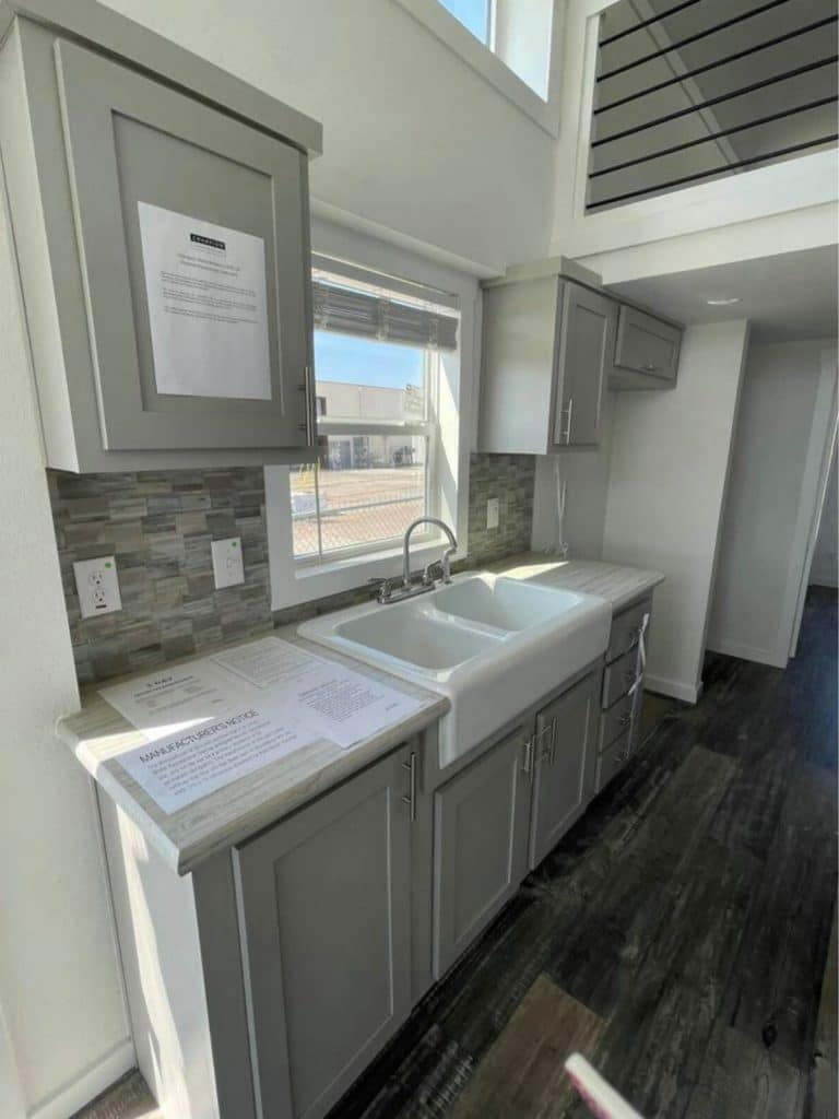 Deep farmhouse sink in gray counters of tiny house kitchen